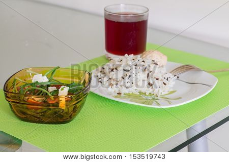 Boiled parboiled wild rice with chicken meatball and salad with arugula, tomatoes and feta cheese. Cherry juice in glass. Colorful dinner on glass table.
