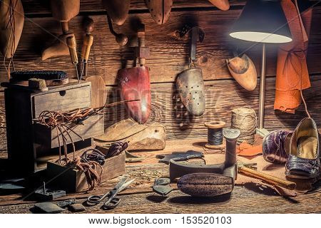 Shoemaker workshop with brush and shoes on old wooden table