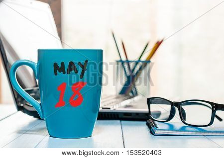 May 18st. Day 18 of month, calendar on morning coffee cup, business office background, workplace with laptop and glasses. Spring time, empty space for text.