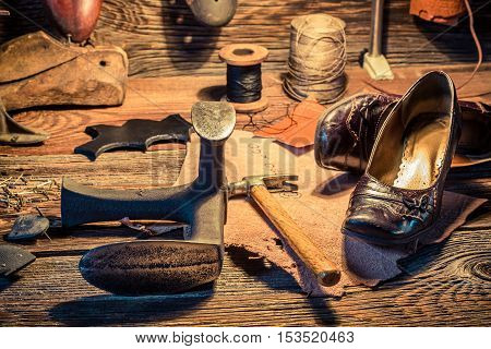 Shoemaker workplace with brush and shoes on old wooden table