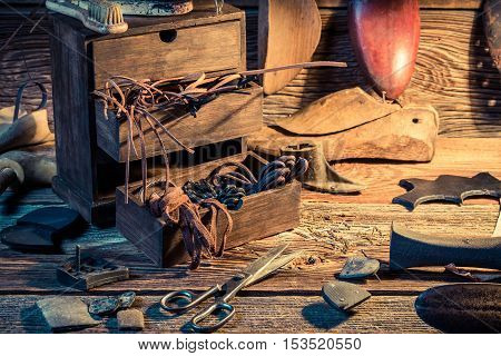 Shoemaker Workplace With Shoes, Laces And Tools