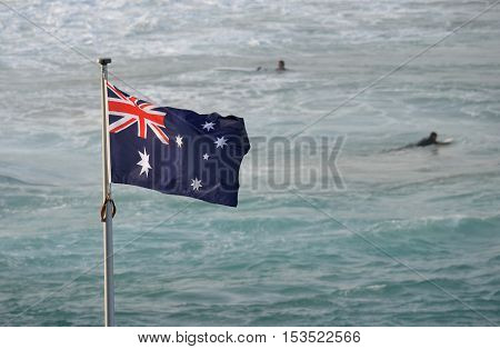 Australian flag waving in the wind. Surfers in the background on the beach.