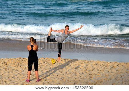 Sydney Australia - Jun 9 2013. Girl doing yoga on the beach. Another girl taking photos. Woman practices Ashtanga Vinyasa yoga Surya Namaskar Sun Salutation asana Urdhva Mukha Svanasana