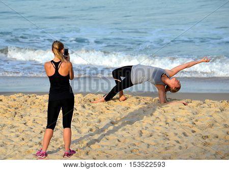 Sydney Australia - Jun 9 2013. Girl doing yoga. Another girl taking photos. Woman practices Ashtanga Vinyasa yoga Surya Namaskar Sun Salutation asana Urdhva Mukha Svanasana