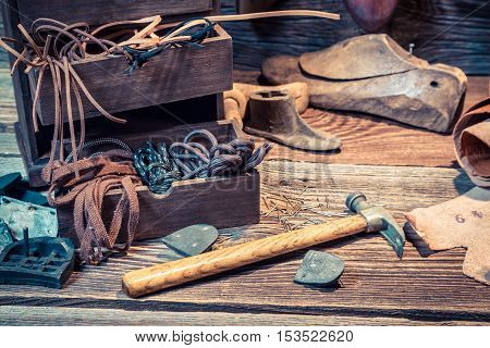 Vintage Cobbler Workplace With Shoes, Laces And Tools