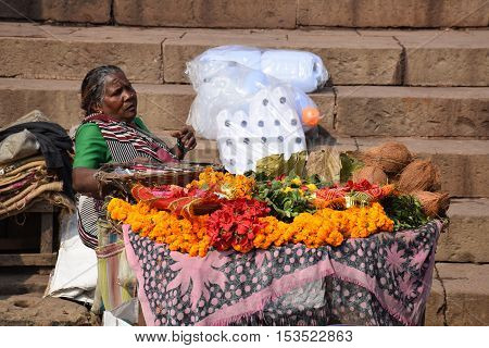 VARANASI, UTTAR PRADESH, INDIA - FEBRUARY 17, 2016 - Unidentified indian woman selling flowers for the afternoon holy Puja ceremony in Varanasi