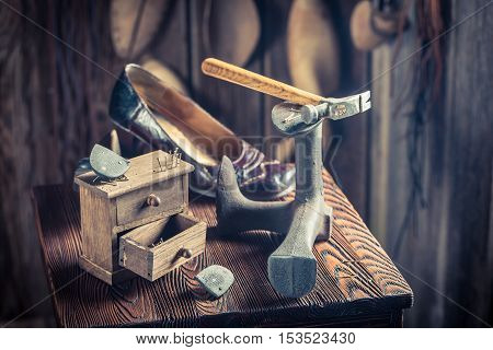 Old Shoemaker Workplace With Tools, Leather And Shoes
