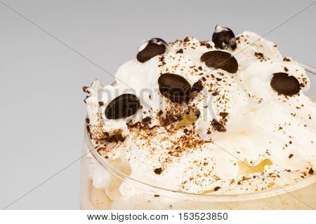 Coffee with whipped cream chocolate and coffee beans on gray background.