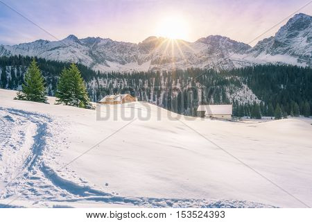 Winter in Austrian mountain village - Picturesque winter scenery on a sunny December day in Ehrwald Austria with the sun warming up the peaks of the Alps mountains covered in snow and fir trees.