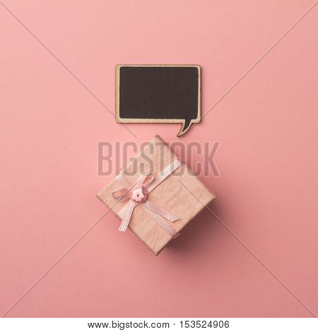 top view of small gift box on pink background with wooden black chalk board speech bubble for text