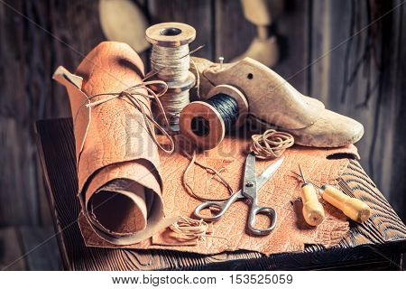 Aged Cobbler Workplace With Tools, Shoes And Laces