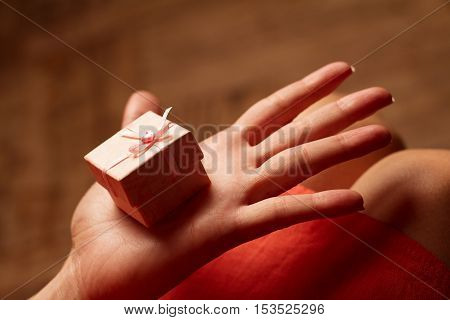 Horizontal side view of an open hand of a woman holding a small pink gift box