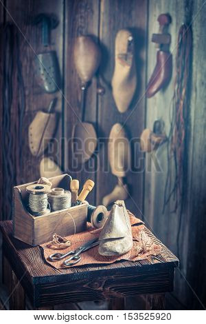 Small Shoemaker Workplace With Shoes, Laces And Tools