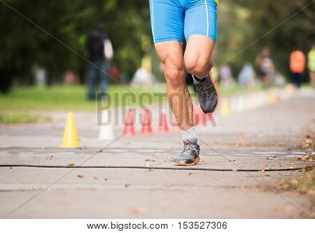 Unrecognizable runner sprinting outdoors. Sportive man training in a urban area, healthy lifestyle and sport concepts.