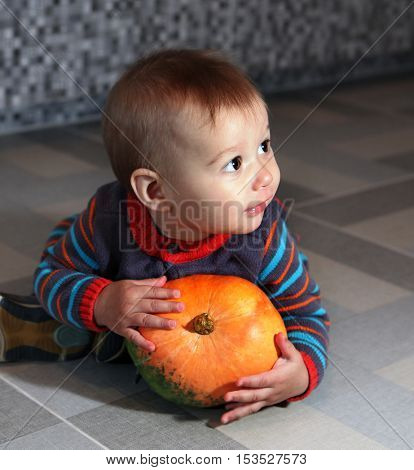 little boy of eight months holding not big orange pumpkin