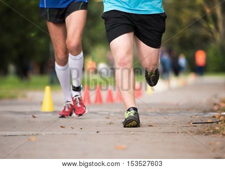 Two unrecognizable runners sprinting outdoors. Sportive people training in a urban area, healthy lifestyle and sport concepts.
