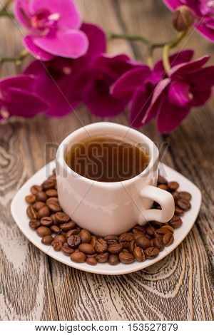 Small white cup of coffee roasted coffee beans orchid on wooden background