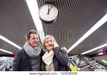 Beautiful senior couple standing at the underground platform, waiting. Woman with smart phone making phone call.