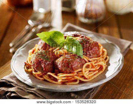spaghetti and meatballs dinner with basil garnish