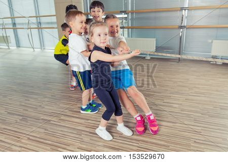 Group of kids pulling a rope in fitness room.