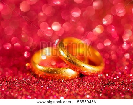 Two old golden wedding rings on bright red blurred sparkle background. Selective focus