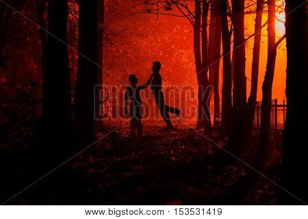 Maniac strangling hands on his victim. Murder in the park. Maniac kills his victim in the night deserted park. Silhouettes in night foggy forest