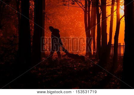 Maniac drags his dead victim. Maniac kills his victim in the night deserted park. Silhouettes in night foggy forest