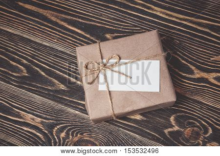 Vintage gift box with blank gift tag on old wooden background