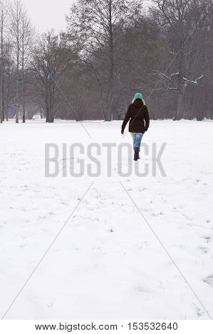 rear view of woman walking across snow covered field in winter. with copy space.