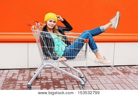 Fashion Beautiful Woman In Trolley Cart Wearing Black Jacket Hat Over Colorful Orange Background