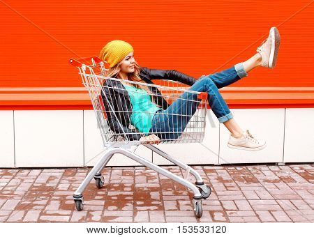 Fashion Pretty Cool Girl In Trolley Cart Wearing Black Jacket Hat Over Colorful Orange Background