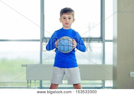 Little boy playing basketball blue ball and form.
