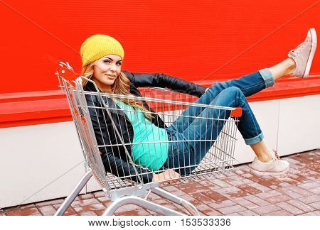 Fashion Woman In Trolley Cart Wearing Black Jacket Hat Over Colorful Orange Background
