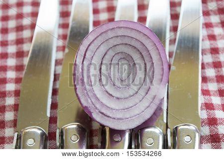 Tropea onion cut half on background of steel knife