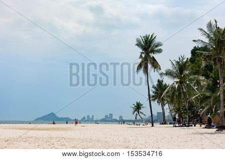 Hua Hin Thailand - October 23 2016: View at city beach at daytime with few tourists sunbathing and coconut trees