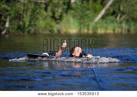 Brunette Woman Riding Wakeboard In A Summer Lake