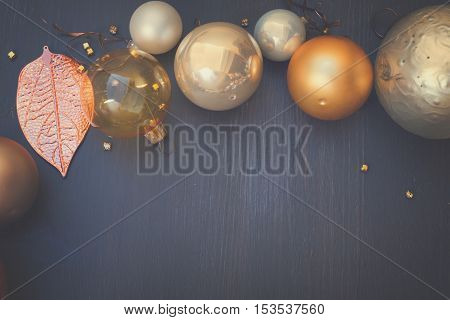 Christmas golden and silver decorations border on dark wooden background with copy space, retro toned