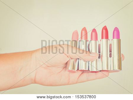 Collection of pink and red shades of shiny lipsticks in hand, retro toned