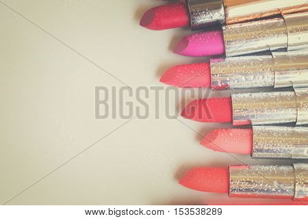 Row of wet lipsticks with copy space on beige background close up, retro toned