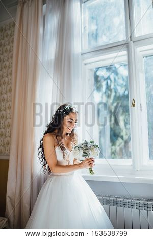 Bride holding wedding bouquet and smiling in hotel