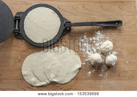 An overview of home made tortillas and a cast iron press.