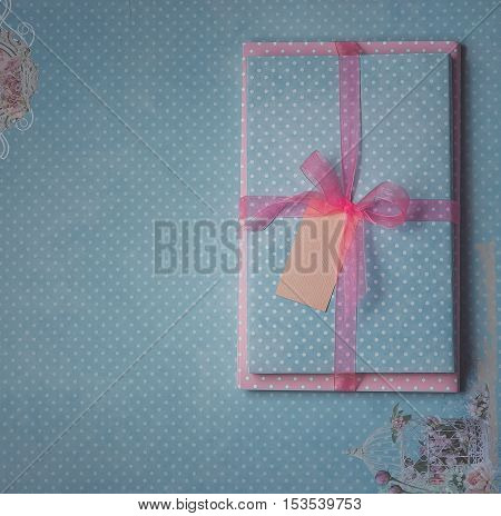 Vintage gift with blank gift tag on craft blue background