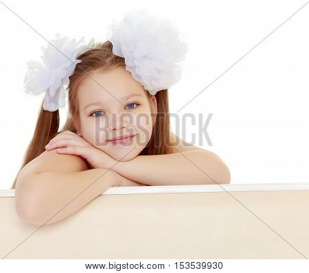 Gentle long-haired little girl with big white bows on the head . She leaned on the windowsill. Close-up.Isolated on white background.