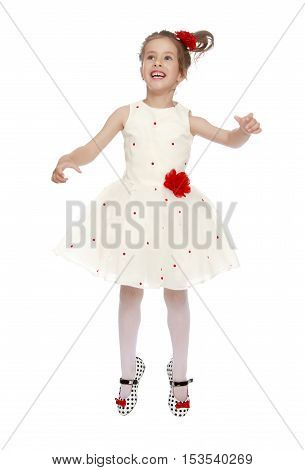 Joyful little Princess dressed in a white dress with a red flower at the waist . Girl jumping gesticulating animatedly - Isolated on white background