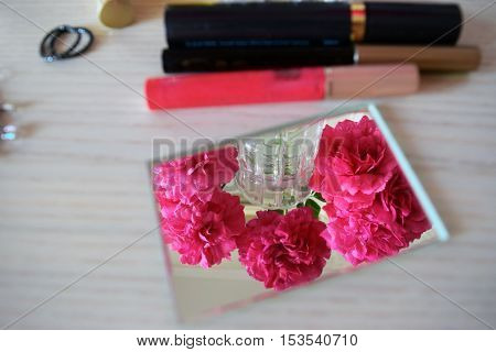 Cosmetics and flowers on the female dressing table.