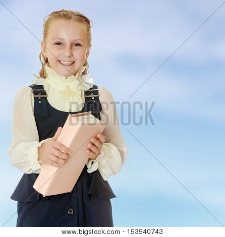 Dressy girl schoolgirl in black dress and white blouse holding a textbook and smiling cheerfully at the camera. Close-up.On the pale blue background.