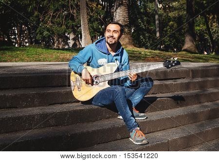 Smiling hispanic man playing acoustic bass guitar at the street