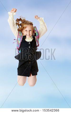 Joyful girl schoolgirl in black dress and white shirt and a knapsack on her shoulders. She jumps, hands up.On the pale blue background.