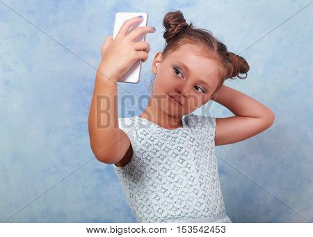 Fun Kid Girl Posing And Making A Selfie Photo On Mobile Phone On Blue Background