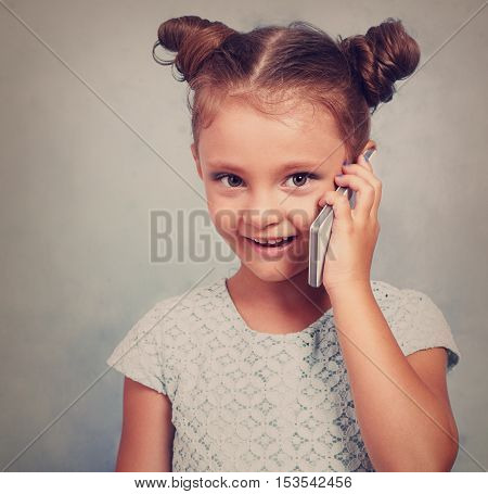 Funny Kid Girl Talking On Mobile Phone With Happy Smile On Blue Background With Empty Copy Space.ton